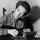 Woody Guthrie nel 1943 con la celebre chitarra contro il fascismo